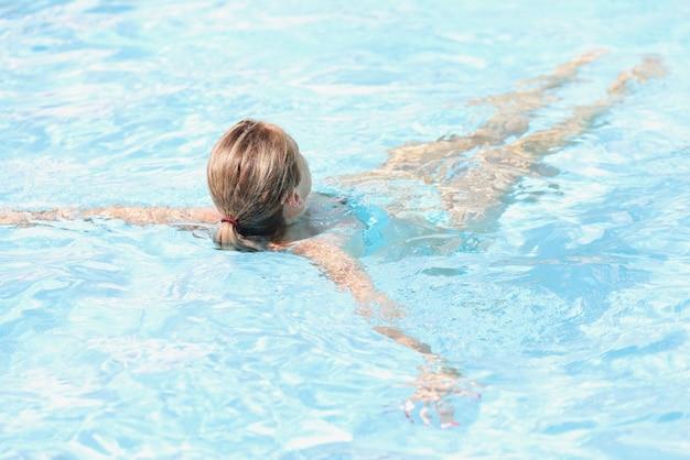 Молодая женщина, плавание в бассейне на отдыхе вид сзади