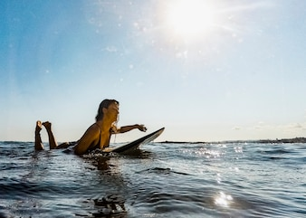 Young woman swimming on surfboard in water