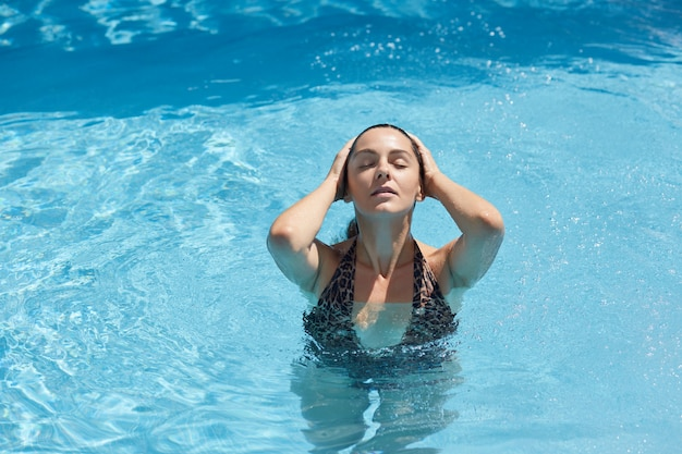 Young woman in swimming pool touching her wet hair and keeping eyes closed, lady in stylish swimsuit posing in blue water, relaxing at spa resort.
