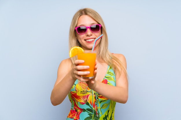 Young woman in swimsuit over blue  with a cocktail