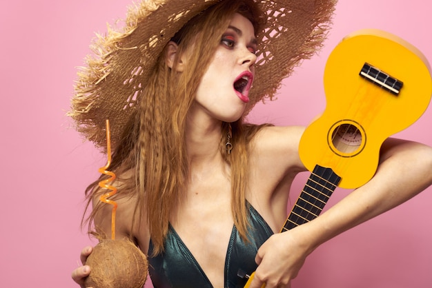 Young woman in a swimsuit and a hat in the studio, fun party, beach at home playing ukulele guitar