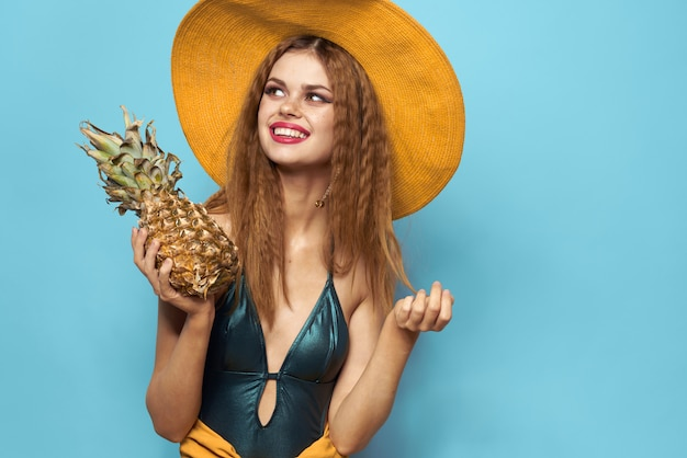 Young woman in a swimsuit and a hat in the studio with pineapple in her hands, blue wall, self-isolation and quarantine fun