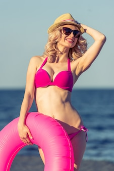 Young woman in swimsuit, hat and sun glasses.