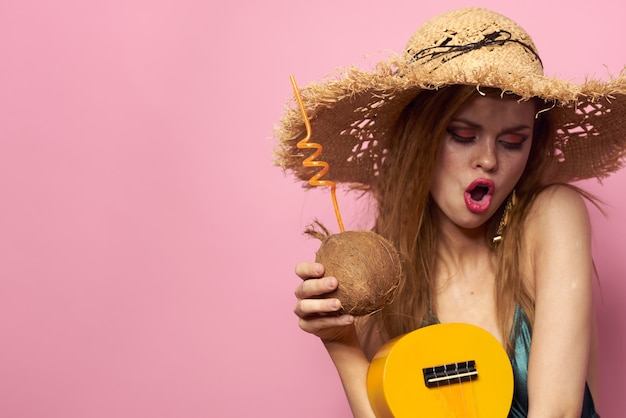 Young woman in a swimsuit and a hat with pineapple in hand, fun party, beach at home playing ukulele guitar