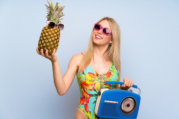 Young woman in swimsuit holding a pineapple with sunglasses and a radio