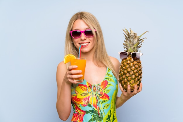 Young woman in swimsuit holding a pineapple with sunglasses
