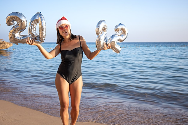 Una giovane donna in costume da bagno e cappello di babbo natale tiene in mano i palloncini di natale
