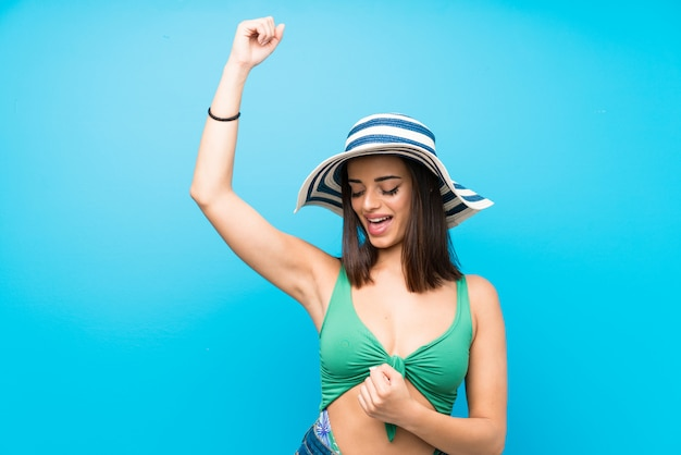 Young woman in swimsuit in summer holidays celebrating a victory