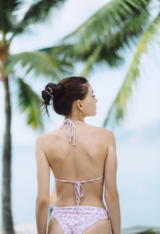 Young woman in a swimsuit on a tropical vacation
