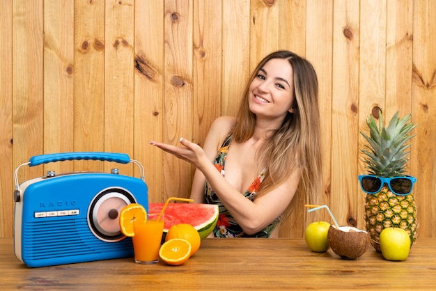 Young woman in swimsuit with lots of fruits extending hands to the side for inviting to come