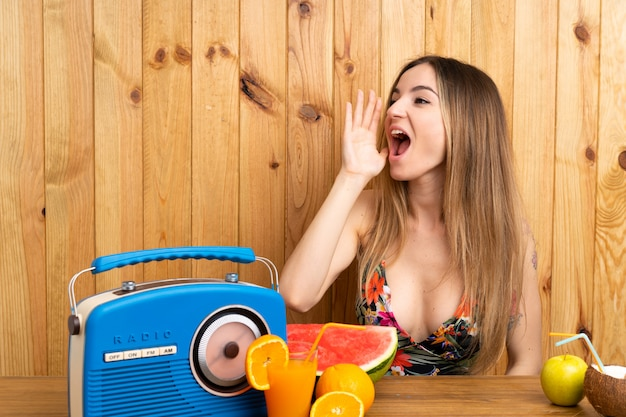 Young woman in swimsuit with lots of fruits shouting with mouth wide open