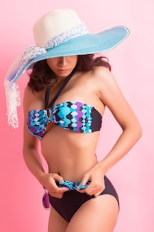 Young woman in swimwear isolated over pink