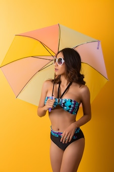 Young woman in swimwear isolated over yellow