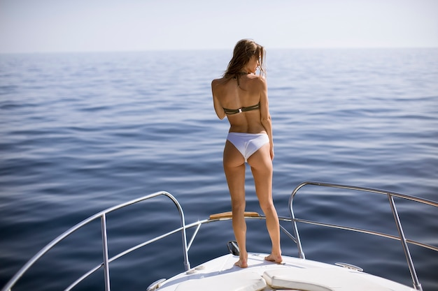 Young woman in swimwear standing on yacht front