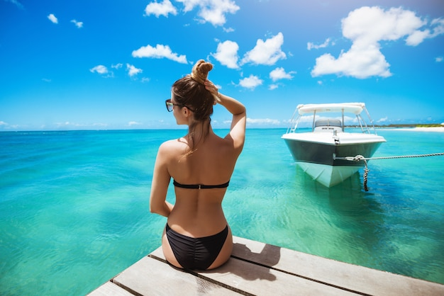 Young woman in swimwear sunbathing hoilding hair up looking away