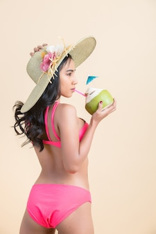 Young woman in swimwear with coconut