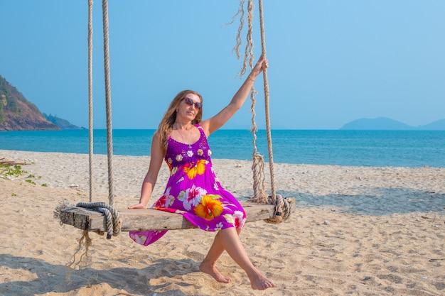 海岸のヤシの木から吊り下げられたブランコに揺れる若い女性。アジアの熱帯諸国への旅行と観光。