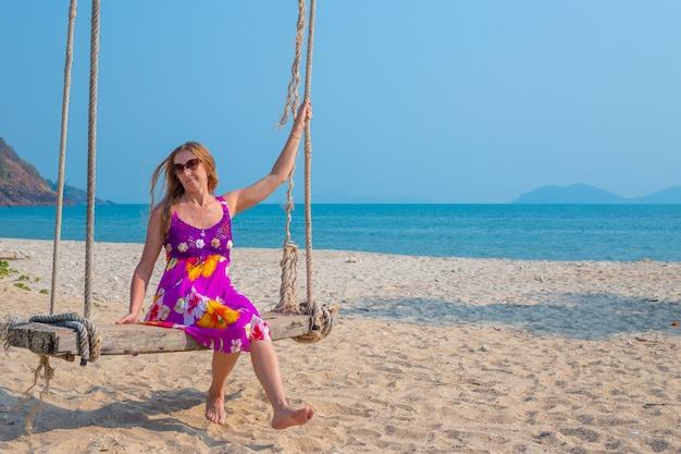 海岸旅行や観光でヤシの木から吊り下げられたブランコに揺れる若い女性