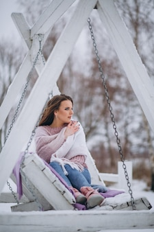 Young woman swinging in a winter park