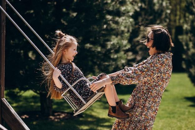 Молодая женщина качается с дочерью на заднем дворе