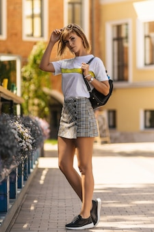 A young woman in a t-shirt and a checkered skirt with a backpack walks along a european street