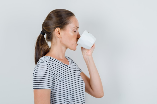 Young woman in t-shirt drinking tea and closing eyes .