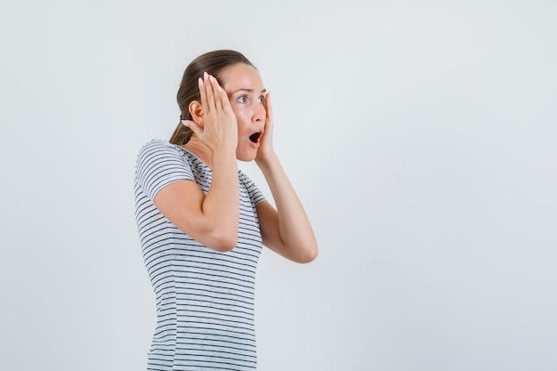 Giovane donna in maglietta tenendo le palme sulle guance e guardando sorpreso, vista frontale.