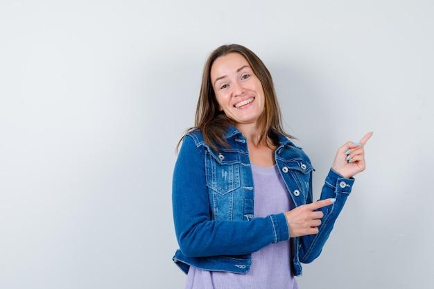 Giovane donna in t-shirt, giacca che punta all'angolo in alto a destra e sembra allegra, vista frontale.