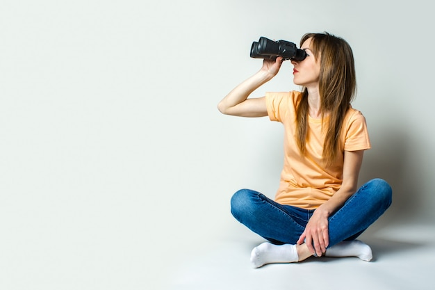Young woman in a t-shirt and jeans sitting on the floor looks through binoculars on a light background