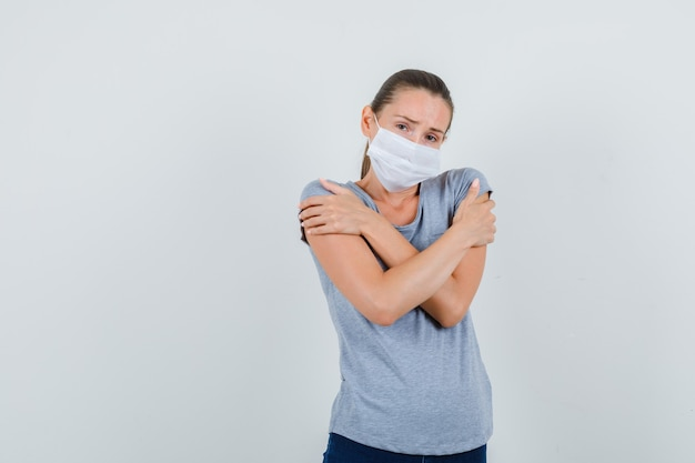 Young woman in t-shirt, mask, jeans hugging herself and feeling cold , front view.