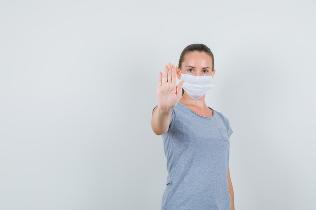 Young woman in t-shirt, mask showing refusal gesture and looking serious , front view.