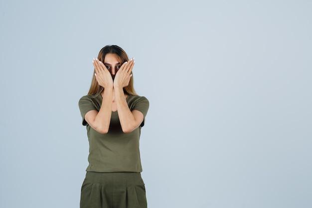 Giovane donna in t-shirt, pantaloni che si tengono per mano sul viso e sembra spaventata, vista frontale.