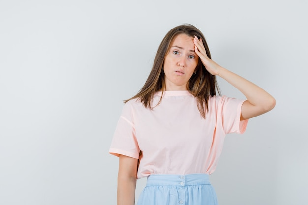 Young woman in t-shirt, skirt touching her forehead and looking puzzled , front view.