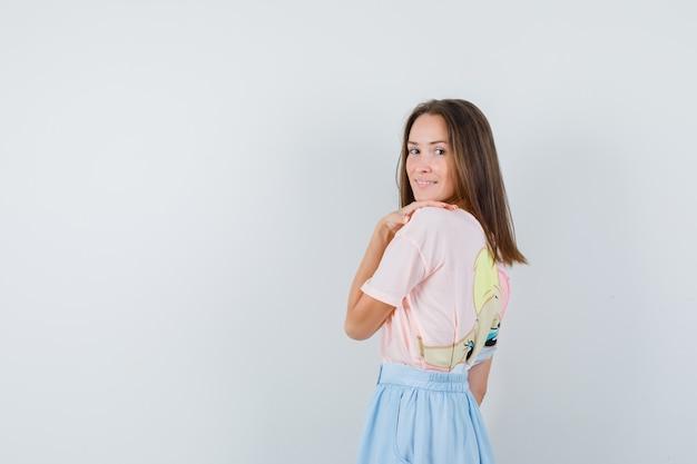 Giovane donna in t-shirt, gonna che tocca la sua spalla e guardando indietro, vista posteriore.