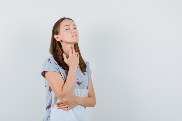 Young woman in t-shirt touching sore throat with fingers , front view.
