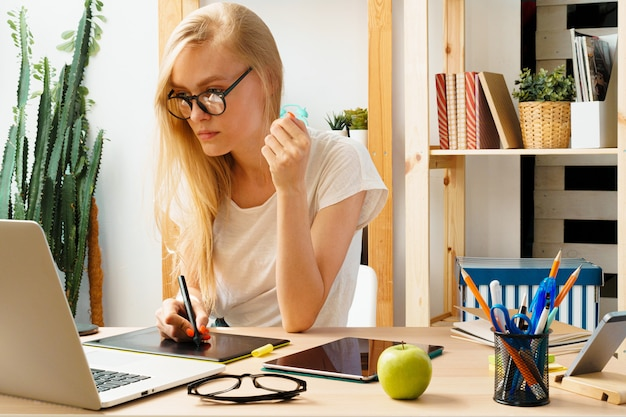 Young woman and tablet working at home office.