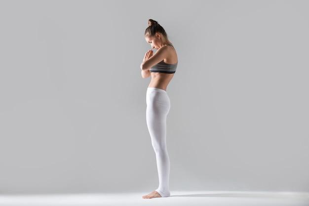 Young woman in tadasana pose with namaste, grey studio background