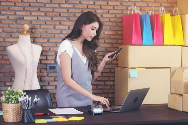 ノートパソコンで仕立て屋の若い女性は、メールに答えています、ビジネスウーマンの起業家の成功。販売オンライン小包配達