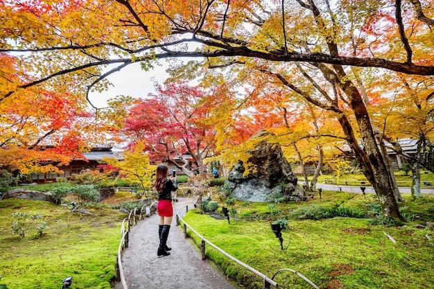 若い女性が秋の公園で写真を撮ります。秋の色とりどりの葉、日本の京都。