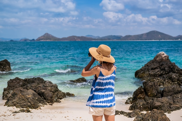 Young woman take a picture at the tropical beach, summer vacation and travel concept