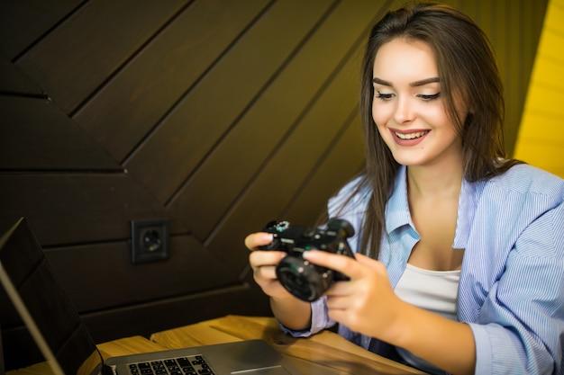 Молодая женщина фотографирует на ретро фотоаппарат, сидя в кафе