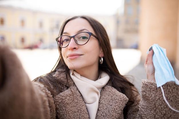 若い女性が自分撮りをします女性がカメラに医療用マスクを見せます視力のための眼鏡をかけた女性