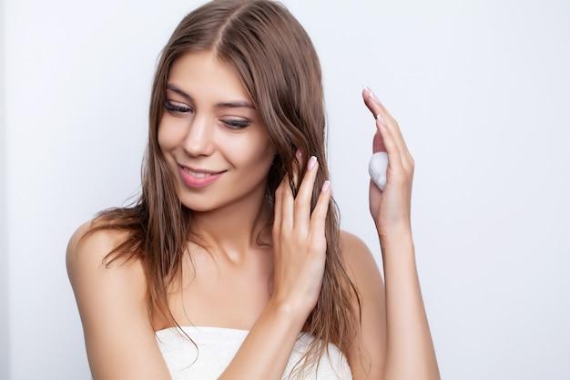 Молодая женщина ухаживает за волосами, используя для ухода за волосами натуральные масла и кондиционеры.