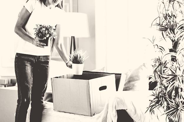 Молодая женщина достает из картонной коробки любимые растения. переезд в новую квартиру