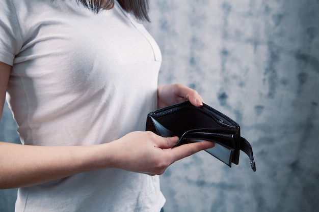 A young woman takes her wallet out of her pocket on a gray