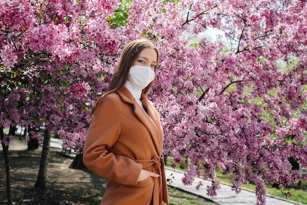 A young woman takes off her mask and breathes deeply after the end of the pandemic on a sunny spring day