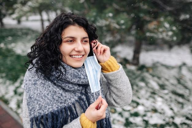 젊은 여자는 추운 서리가 내린 날에 겨울 눈 덮인 공원에서 의료 멸균 마스크를 벗습니다.