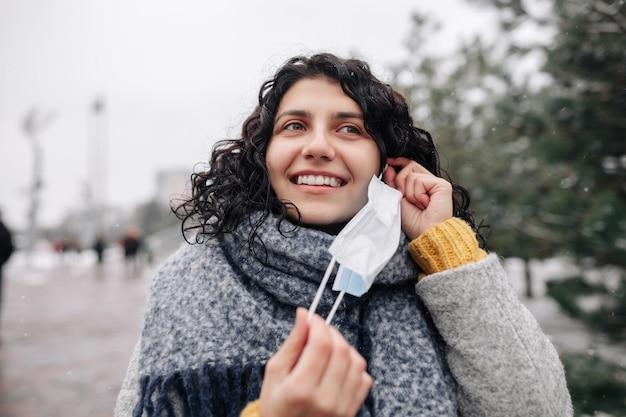 젊은 여자는 추운 서리가 내린 날에 겨울 눈 덮인 공원에서 의료 멸균 마스크를 걸립니다.