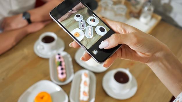 若い女性は、木製のテーブルのクローズアップでモダンなスマートフォンでさまざまなおいしいケーキやティーカップの写真を撮ります