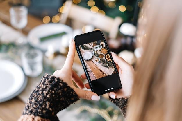 若い女性はスマートフォンでクリスマスのお祝いのテーブルの写真を撮ります。閉じる